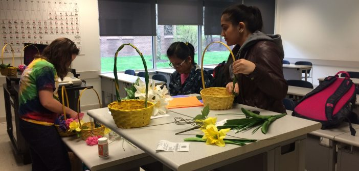Three members of the biology club decorates baskets.