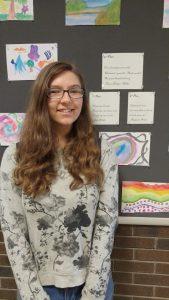 Treva Noakes-Miller standing next to her winning haiku.