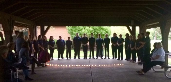 """West Clermont By Request singing """"Heroes"""" by Alesso, standing behind the candles."""