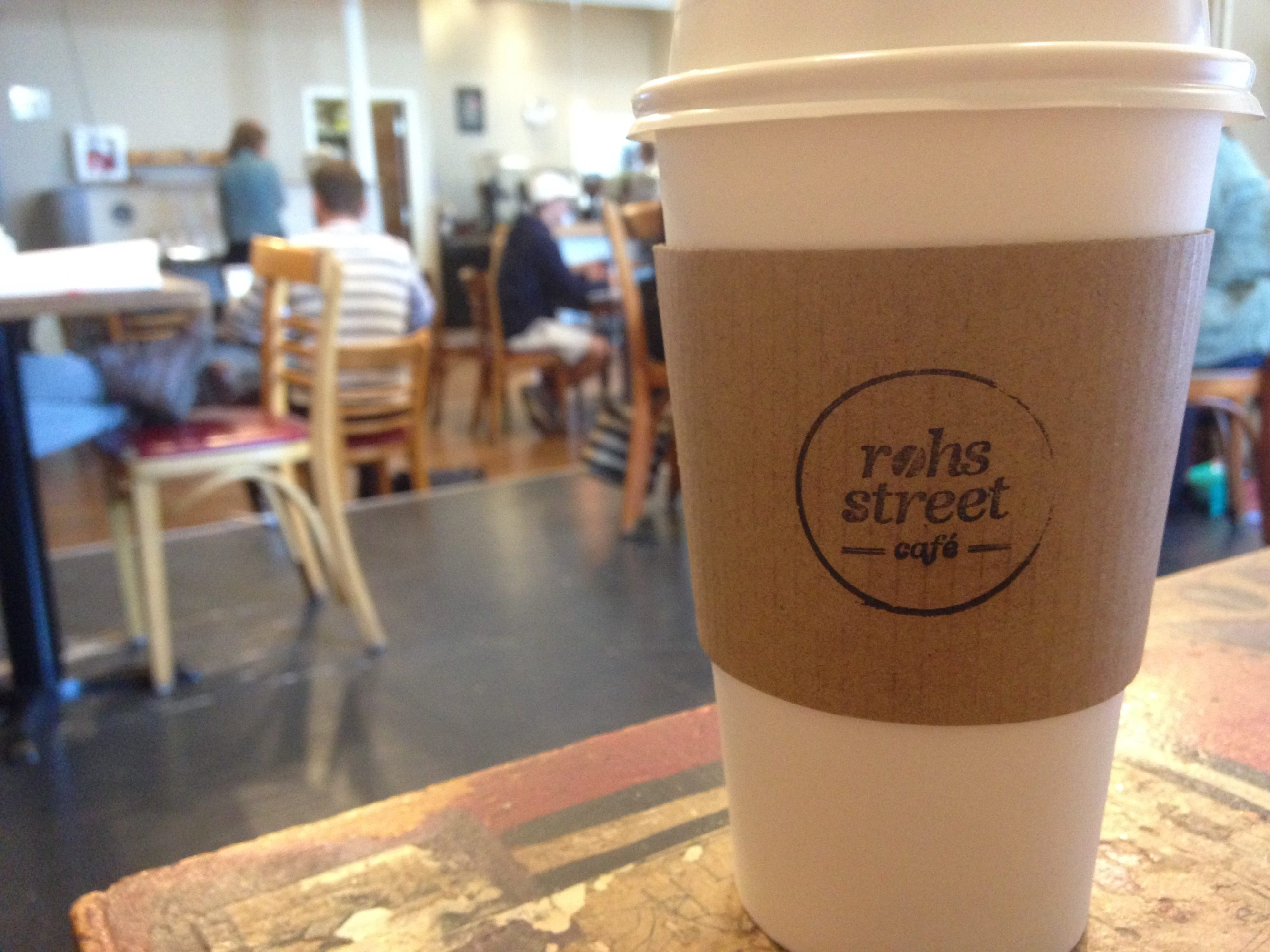 The simple Rohs Street Cafe logo printed on a coffee cup, with the cafe in the background